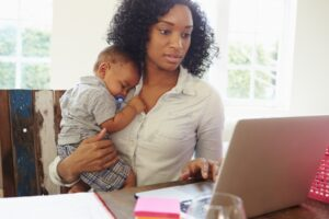 woman-holding-baby-while-researching-on-computer